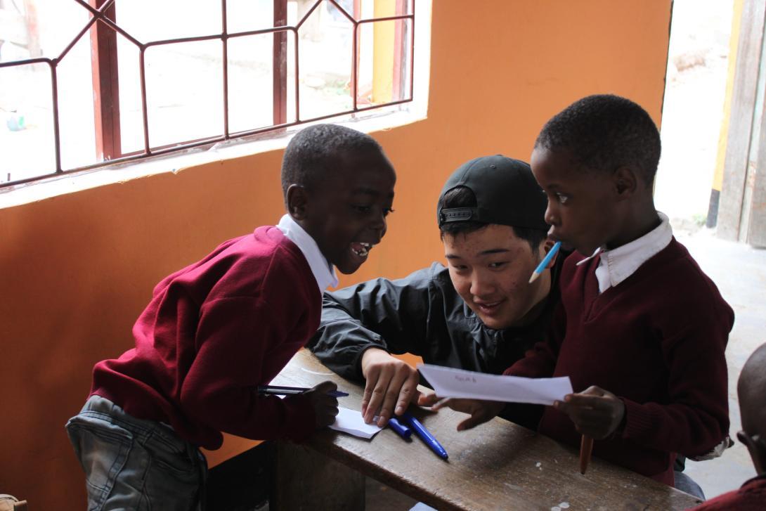 Un joven ayuda a dos niños a practicar sus habilidades en inglés durante su voluntariado para adolescentes en verano.